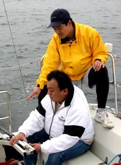 ティラーを握る加藤氏、スキッパーの村上氏の写真