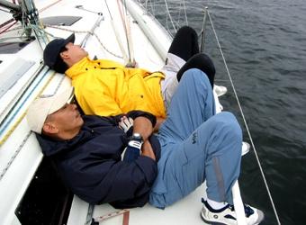 デッキで寝転がるクルーの写真、ほのぼの?