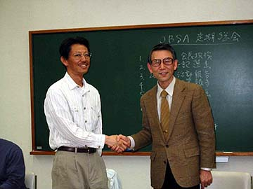 壇上で握手する二人の写真